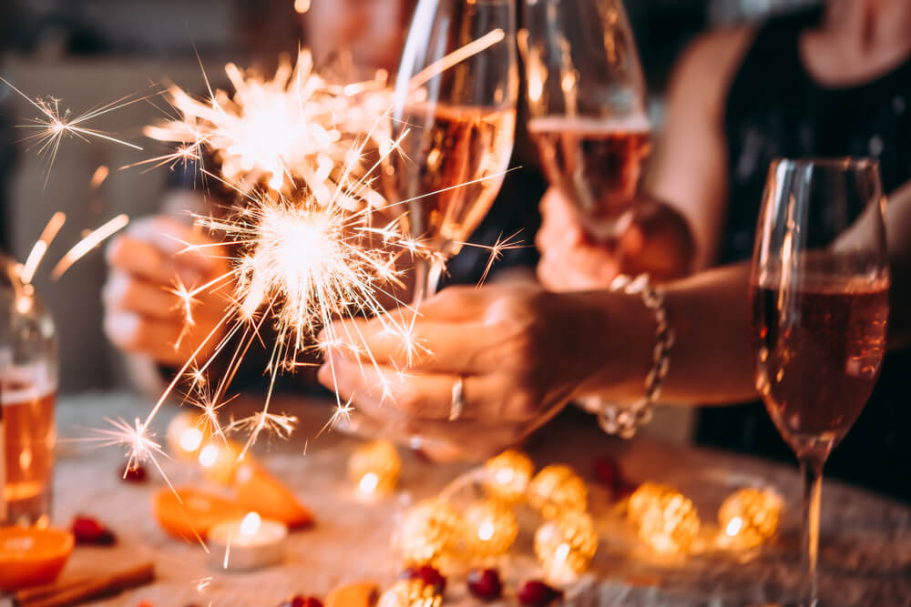 Women holding glasses of wine & sparklers