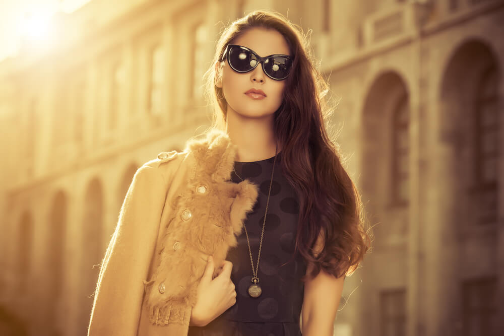 Woman wearing sunglasses, a black dress and a fur coat