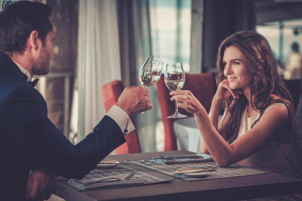 Man and woman at a restaurant each holding a glass of wine