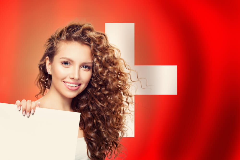 Woman in front of the flag of Switzerland