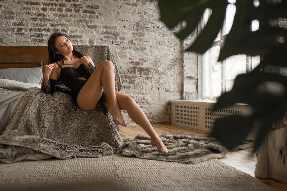 Model wearing black underwear sitting on fur blanket