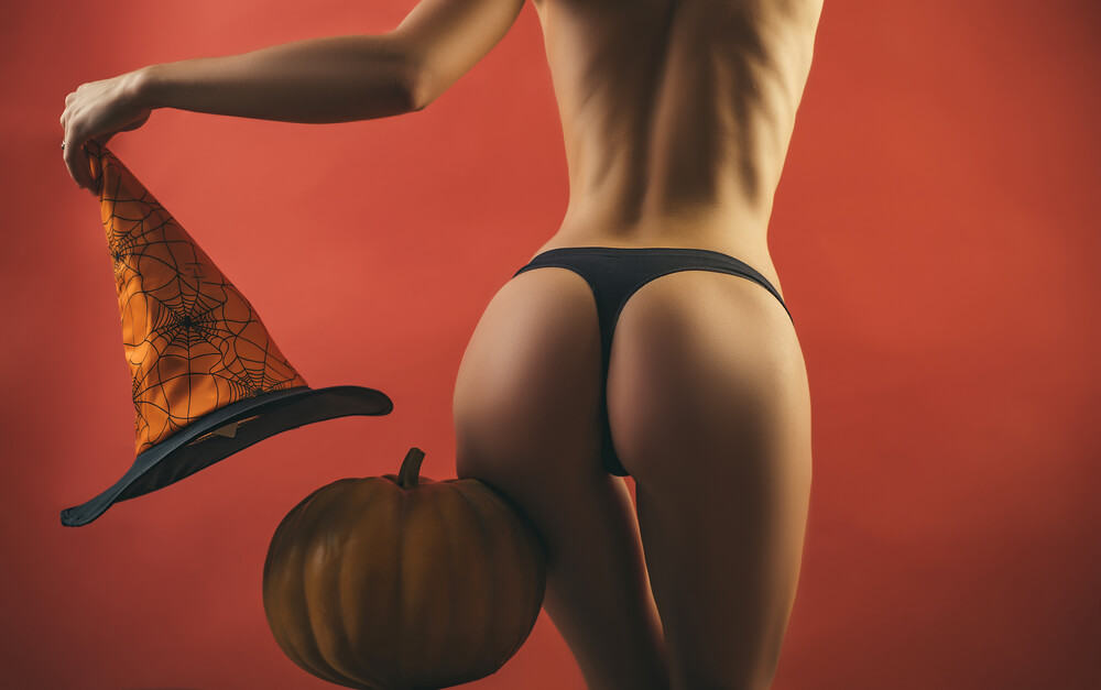 Woman wearing panties holding a witches hat