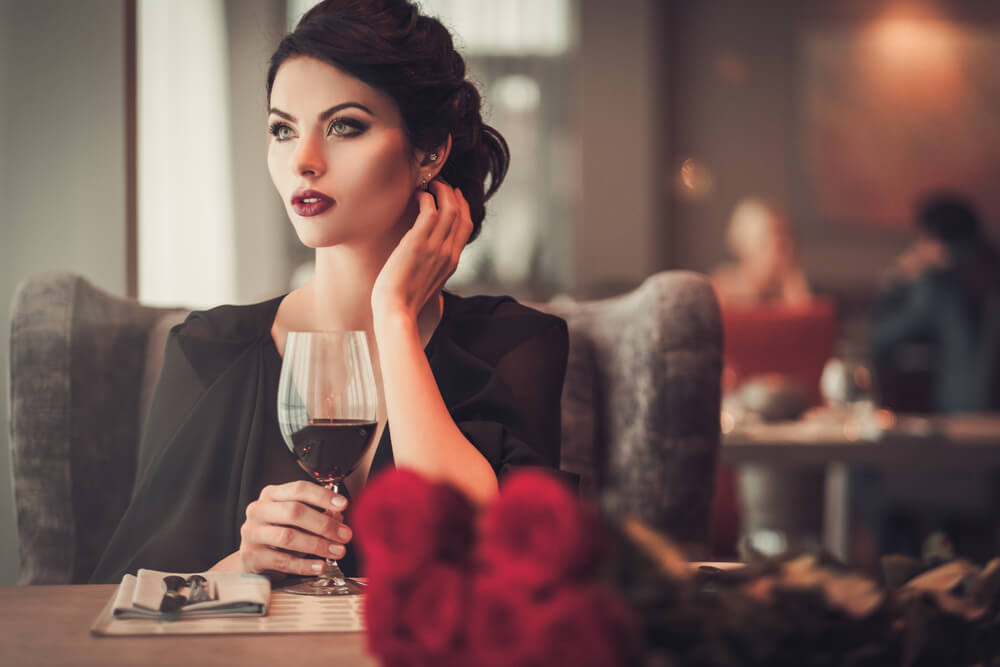 a lady in restaurant drinking red wine