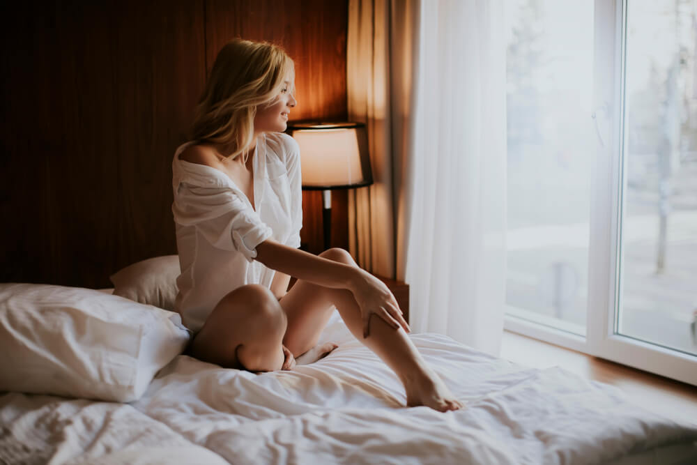 Woman wearing white shirt sitting on a bed